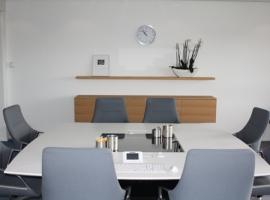 Quarta vergadertafel in kleine spreekruimte bij zorgverzekeraar.